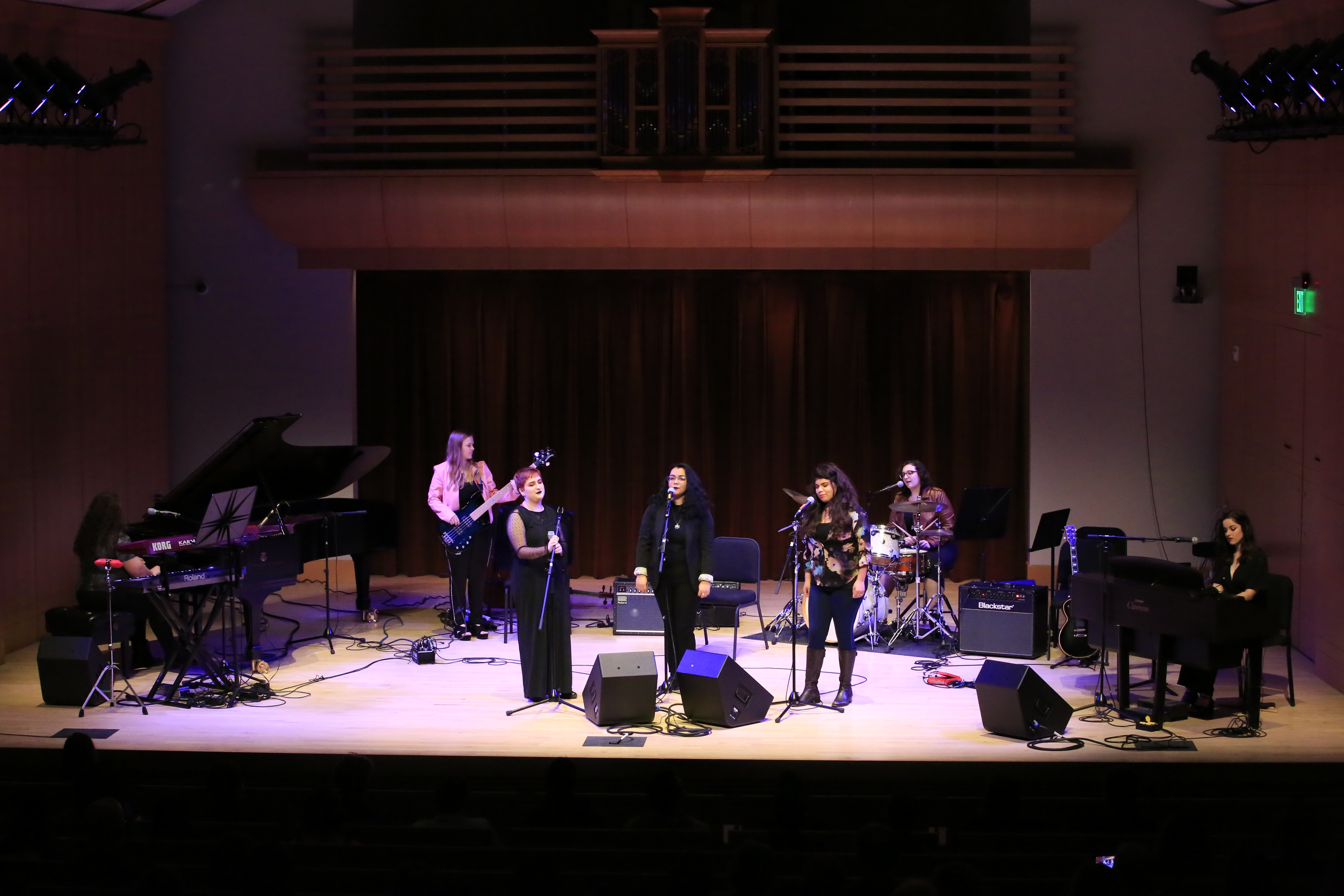 Band of women playing on stage with three singers front and center on Schroeder Hall stage