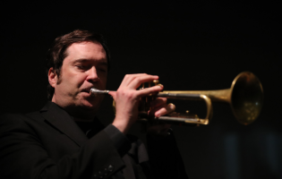 Ian Carey dressed in black and playing trumpet