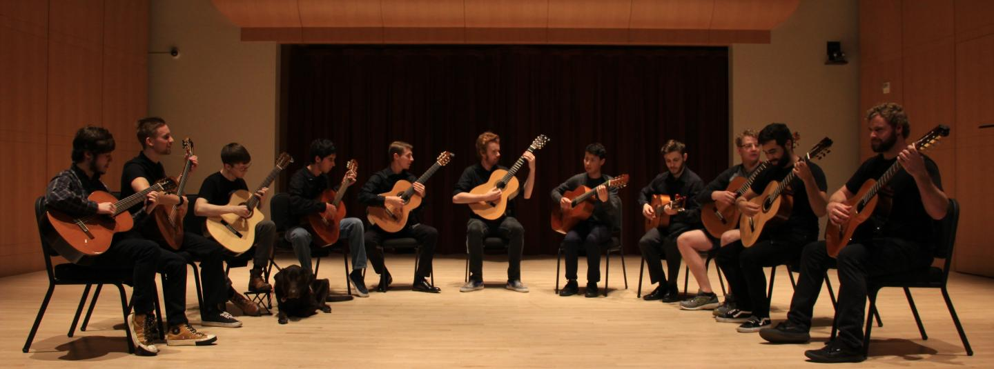 Guitar ensemble in a half circle on stage
