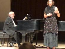Singer standing in front of piano and pianist and singing