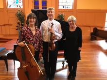 Cellist, violinist, and pianist standing together with their instruments