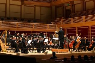 Orchestra onstage with Alex Kahn conducting