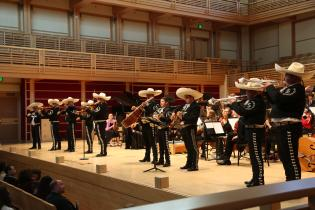 Mariachi band playing on stage with the orchestra