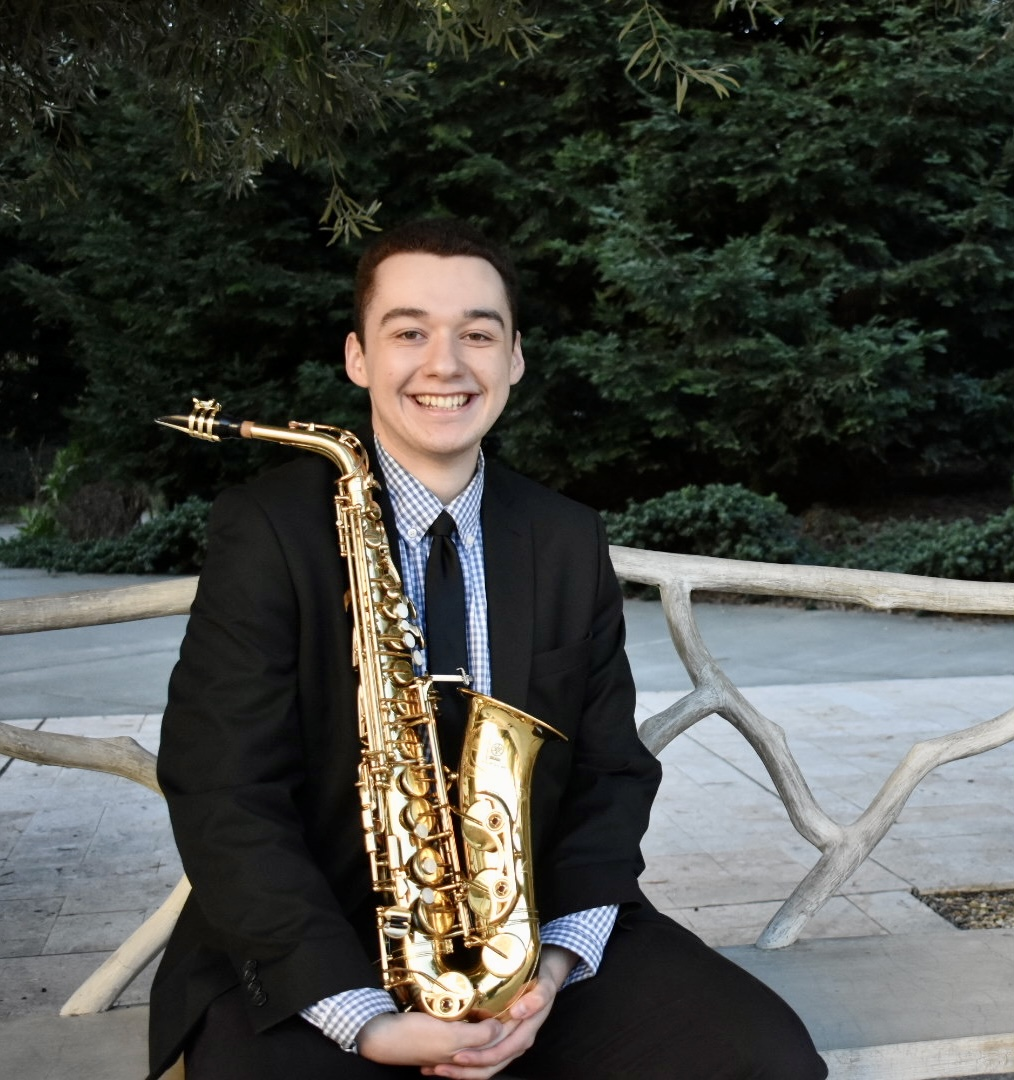 Matthew Bowker headshot holding a saxophone and sitting on a bench outdoors