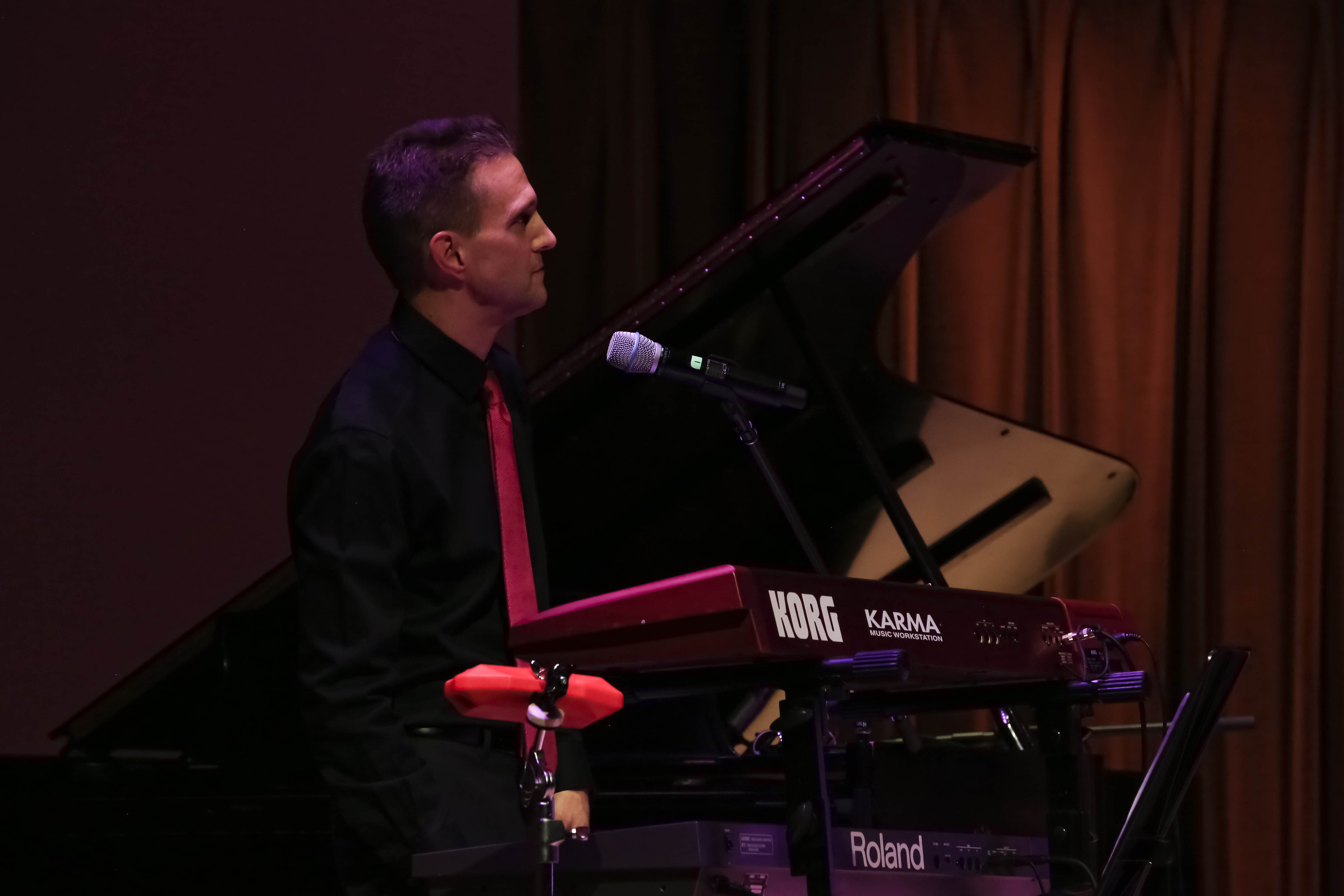Side profile shot of John Palmer playing keyboards and