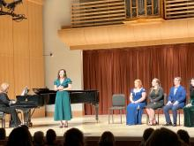 Four students sitting on stage while one student sings in front of a piano and pianist with the silhouette of the audience in the foreground