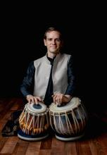 William Rossel sitting with Tabla drums