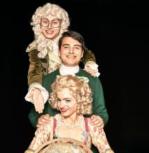 Three actors dressed in period costumes in a vertical line