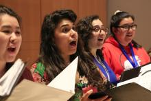 Women singing with choral folders
