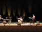 Band onstage at Weill Hall with drums, guitars, sax, and background lighting