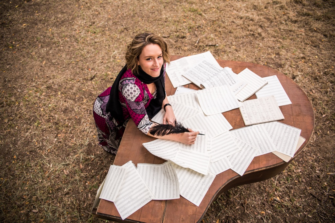 Christa Durand sitting in front of a table of sheet music